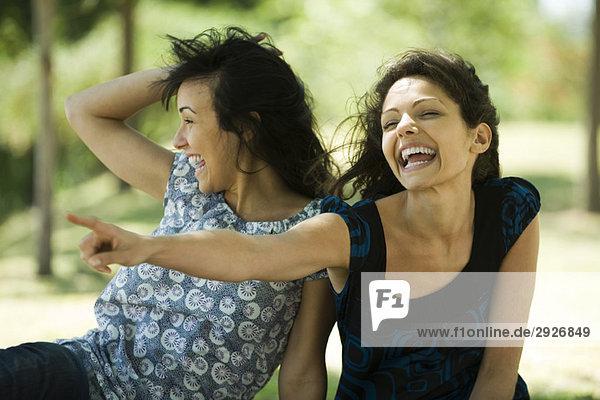 Zwei junge Frauen  die im Freien lachen  eine davon zeigt