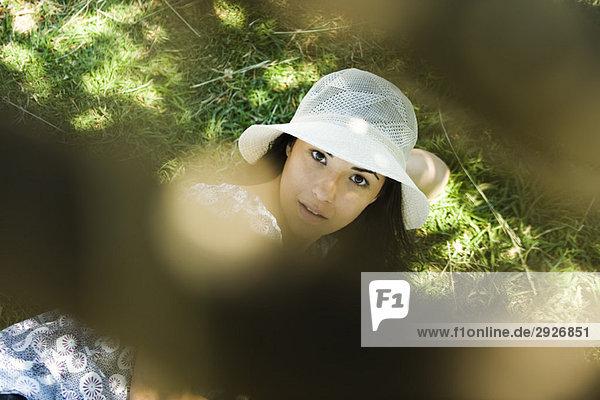 Junge Frau mit Sonnenhut auf dem Boden liegend  Blick in die Kamera  selektive Fokussierung