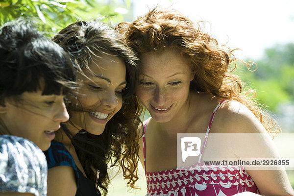 Drei junge Frauen im Freien  die alle lächelnd nach unten schauen.
