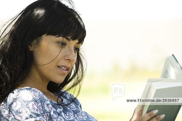 Junge Frau beim Lesen im Freien