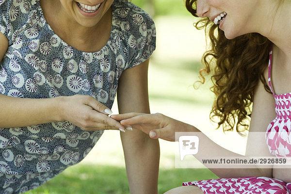 Zwei Frauen  die draußen sitzen und auf die Hand einer Frau schauen  beide lächelnd.