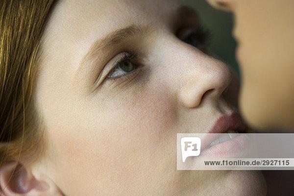 Junge Frau blickt auf das Gesicht des Mannes  extreme Nahaufnahme