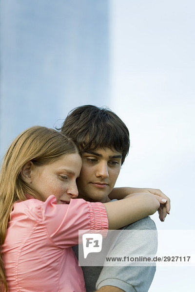 Junges Paar  das sich umarmt und nach unten schaut.