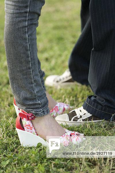 Junges Paar in trendiger Kleidung stehend von Angesicht zu Angesicht  niedriger Schnitt