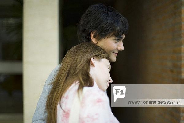 Junge Frau lehnt den Kopf auf die Schulter des Freundes  Seitenansicht