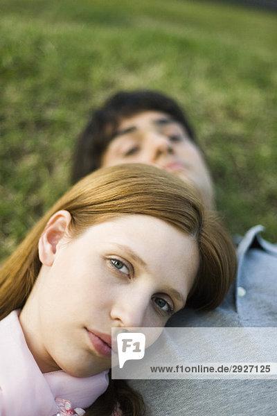 Junges Paar auf dem Boden liegend  Frau mit Kopf auf der Brust des Mannes  Blick in die Kamera