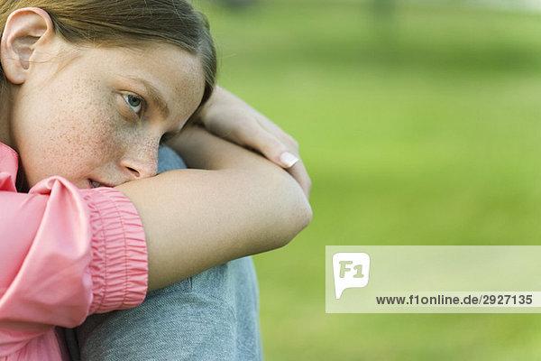 Junge Frau im Freien sitzend mit Kopf auf den Armen liegend  wegschauend