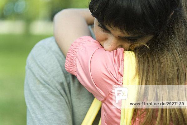 Junges Paar umarmt  Männerkopf auf Frauenschulter  Nahaufnahme