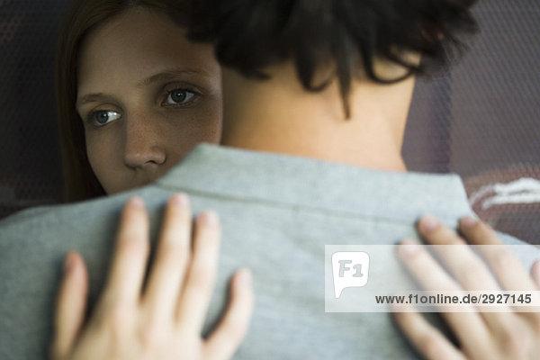 Junges Paar umarmt  Frau schaut weg