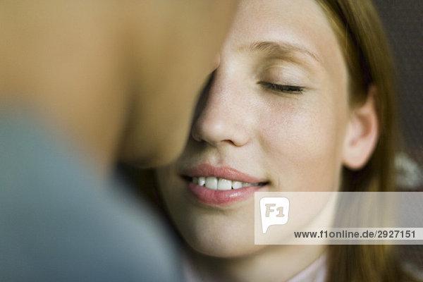 Junge Frau lächelt als Mann ihre Stirn küsst  Augen geschlossen