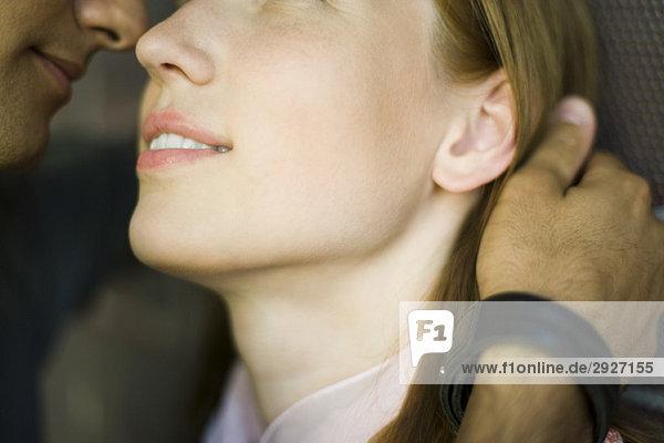 Junges Paar berührt Nasen  Mann streichelt Frauenhaar  abgeschnitten