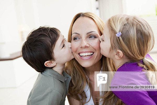 Bruder und Schwester küssen ihre Mutter.