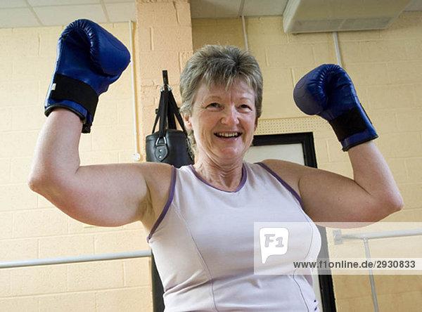Frau gewinnt beim Boxen im Fitnessstudio
