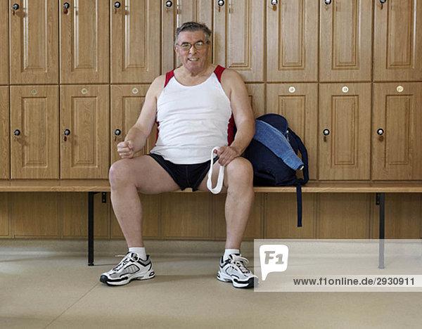 älterer Mann in der Umkleidekabine im Fitnessstudio