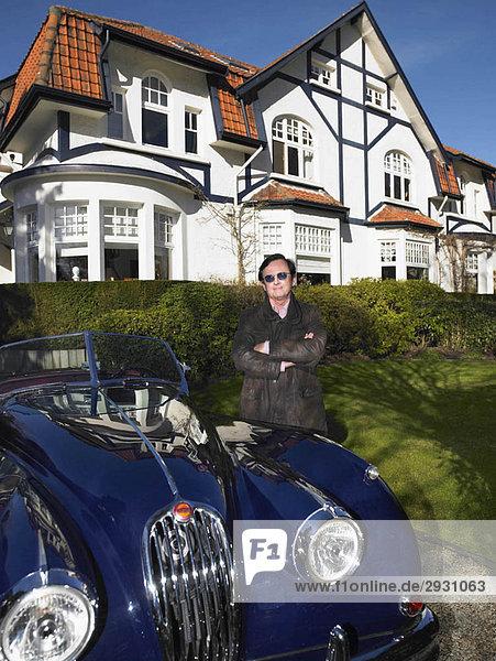 Mann vor seinem Haus und Auto