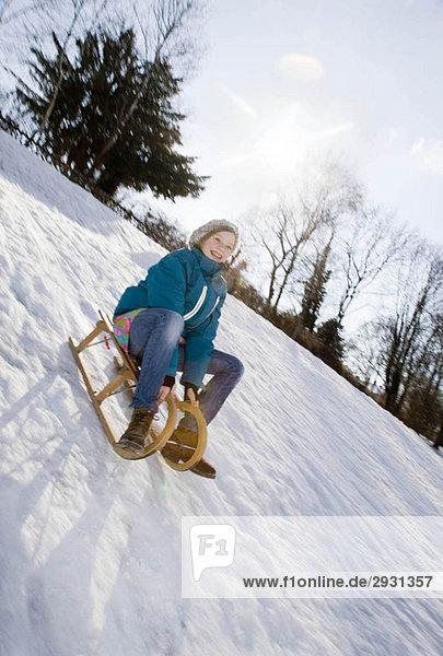 Mädchen beim Schlittenfahren im Schnee