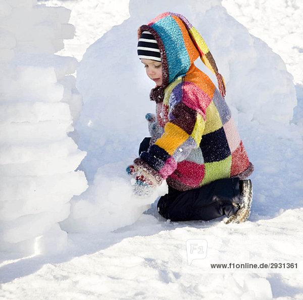 Junge baut Iglu im Schnee