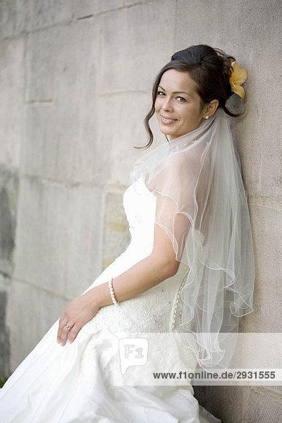 Die Braut posiert in ihrem Hochzeitskleid.