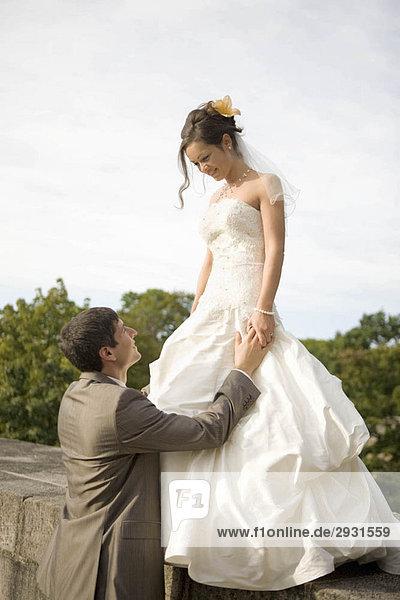 Der Bräutigam schaut zu seiner Braut auf.