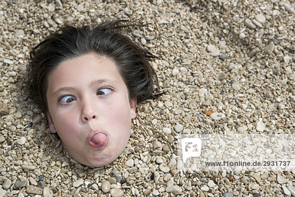 Girl buried in pebbles on beach