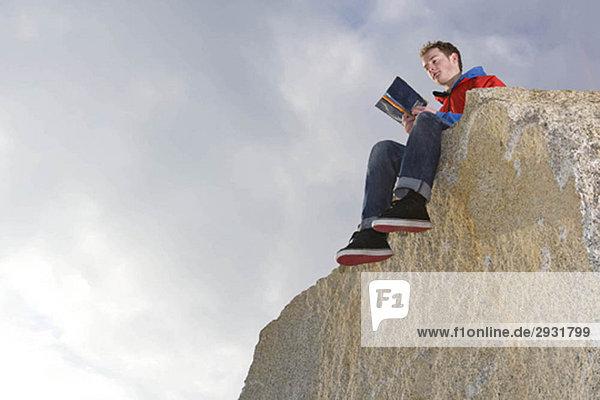Mann liest auf dem Berggipfel