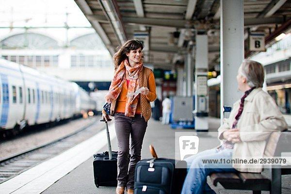 Ein Mann und eine Frau auf einer Plattform am Bahnhof Schweden.