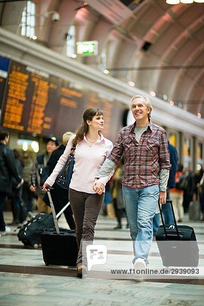 Ein paar mit Koffern am Bahnhof