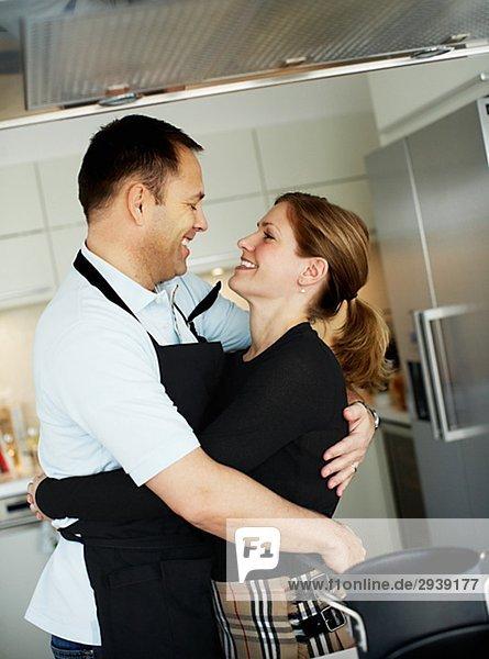 Ein paar steht in einer Küche umarmen Schweden.