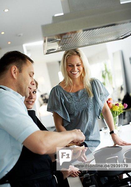 Ein Mann und zwei Frauen machen Abendessen zusammen Schweden.
