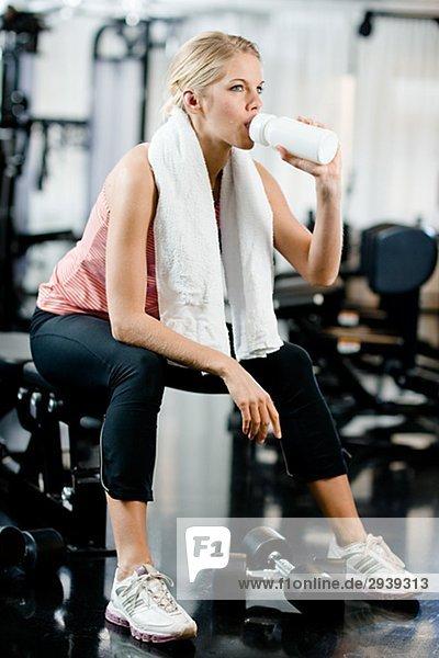 Eine Frau mit einer Flasche Wasser in einem Fitnessstudio Schweden.