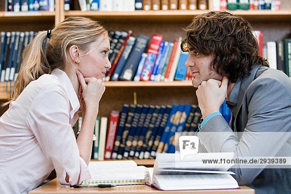 Zwei Studenten sitzen Angesicht zu Angesicht in einer Bibliothek Schweden.