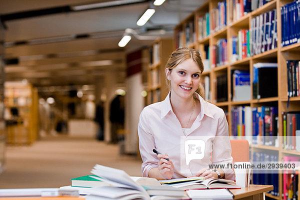 Ein weiblicher Student Studium in einer Bibliothek Schweden.
