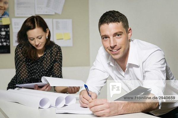 Zwei Personen arbeiten am Schreibtisch