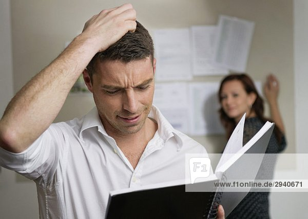Gestörter Mann mit Notizbuch im Büro