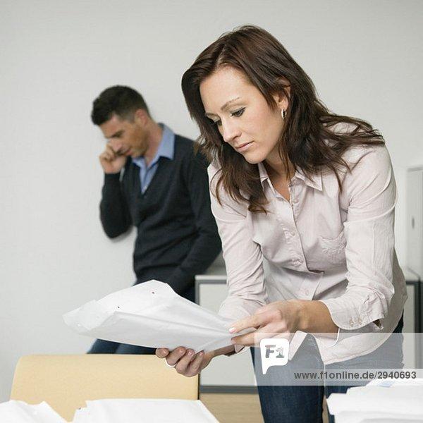 Geschäftsfrau mit Unterlagen  Mitarbeiterin im Hintergrund