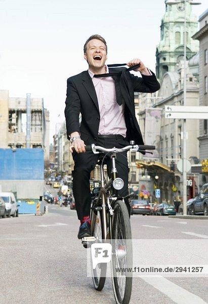 Mann auf dem Fahrrad löst Krawatte