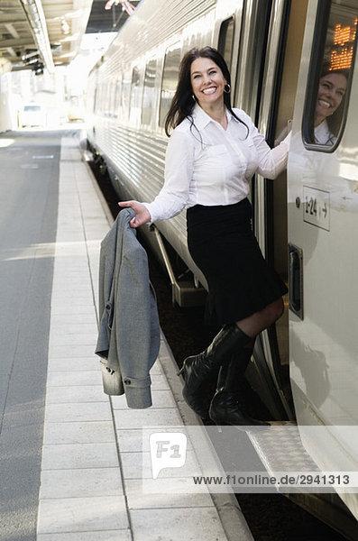 Geschäftsfrau beim Einsteigen in den Zug