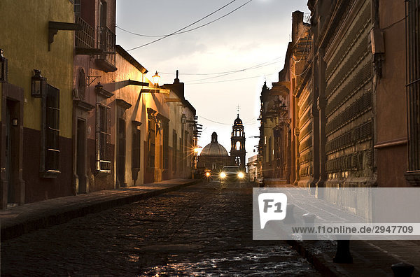 Car Driving down a street at Night  with the Church of San Francisco (Temple de San Francisco) in the background  San Miguel de Allende  Guanajuato  Mexico