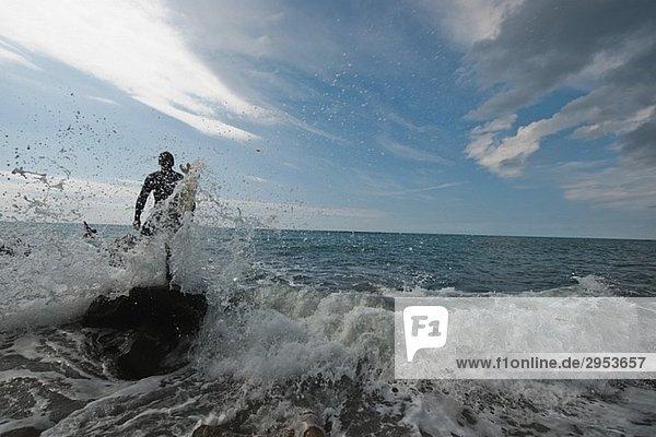Junger Mann in schweren Wellen des Ozeans mit surfboard