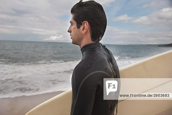 Junger Mann im Anzug seine Surfboard hält