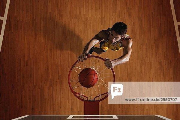 Junger Mann Korbball Basketball in hoop