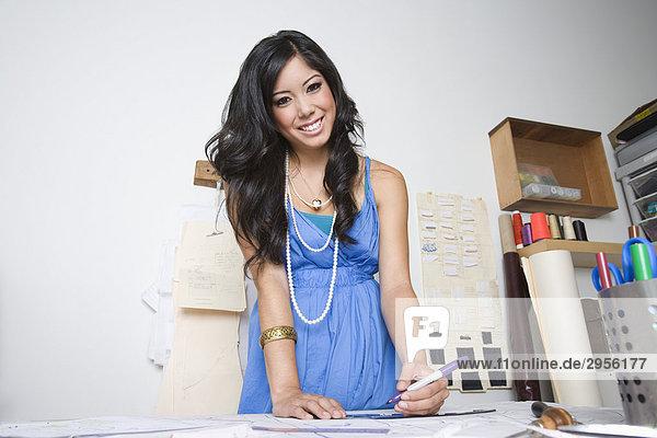 Portrait einer Modedesignerin die an Schreibtisch arbeit