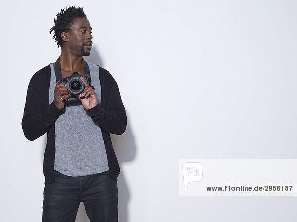 Mittelalter (30-35 Jahre) Fotograf der Kamera hält  Studioaufnahme