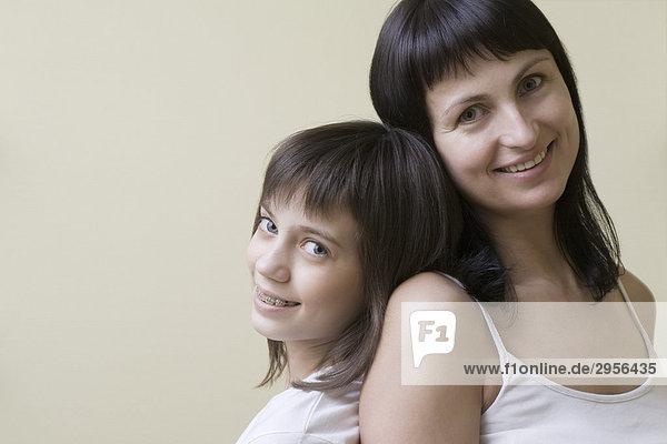 Studioportrait einer lächelnden Mutter und Tochter