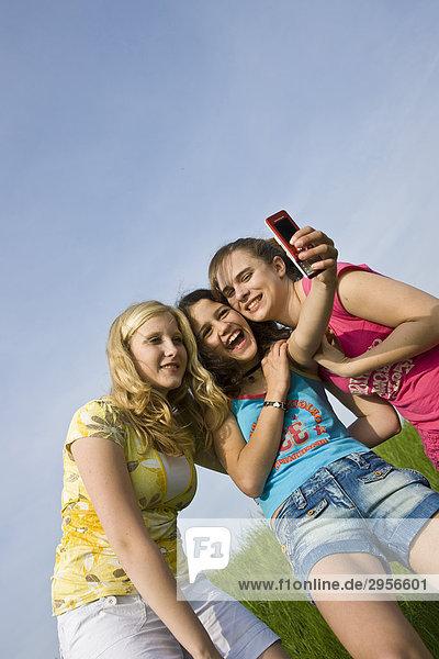 Drei junge Mädchen machen Fotos von sich  Flachwinkelansicht