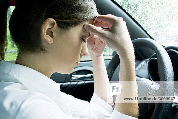 Frau mit Kopfschmerzen im Auto