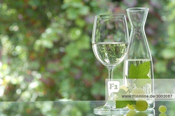 Weißwein in der Karaffe mit Glas und Trauben Weißwein in der Karaffe mit Glas und Trauben