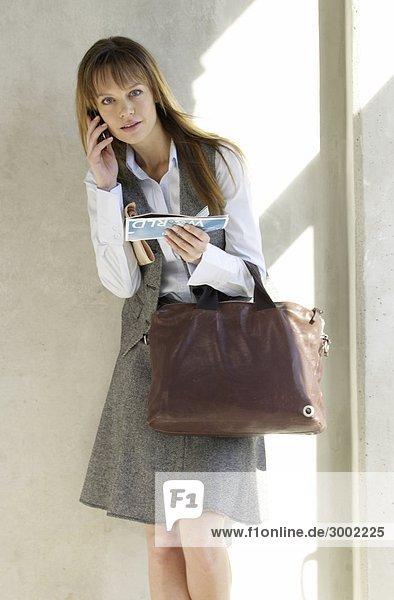 Frau mit Tasche und Flugticket telefoniert