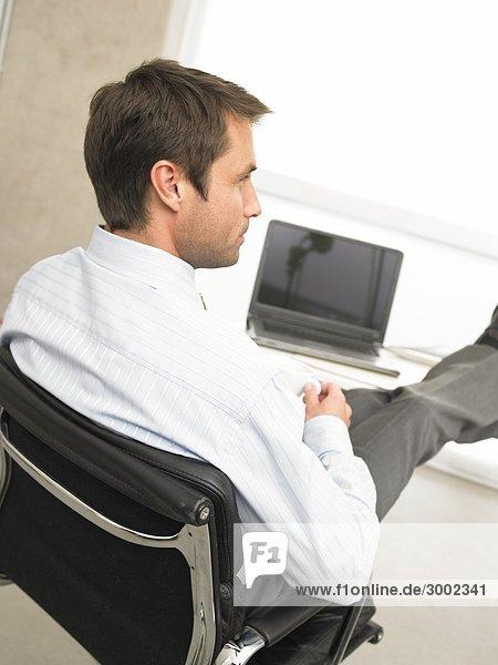 Geschäftsmann am Schreibtisch mit Tasse legt Füsse hoch