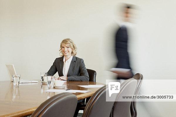 Geschäftsfrau im Konferenzraum und vorbeigehende Person im Hintergrund  München  Bayern  Deutschland